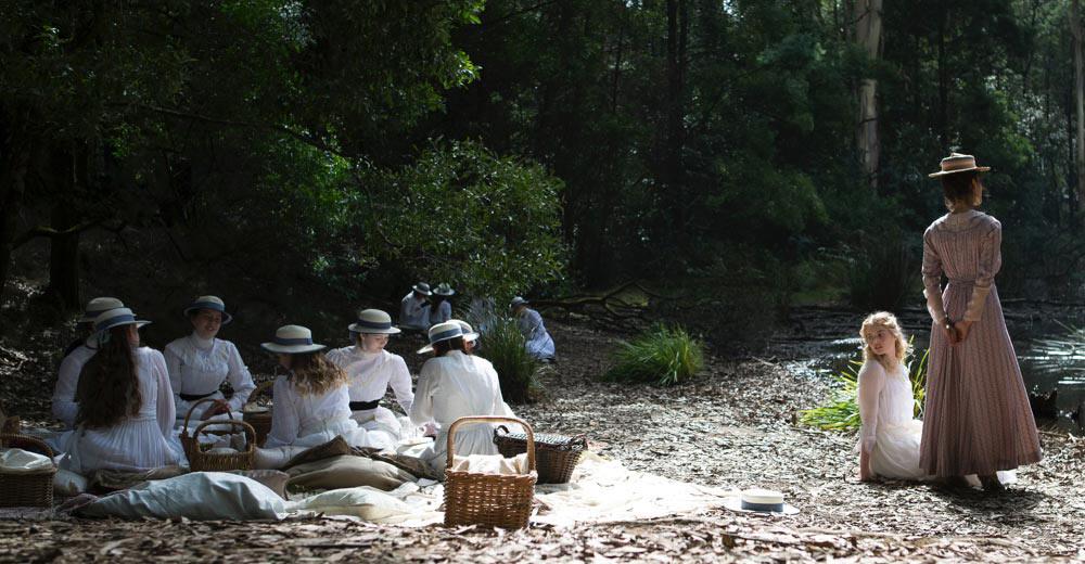 Die Schülerinnen des Appleyard College sitzen in weißen Kleidern auf dem Waldboden beim Hanging Rock.