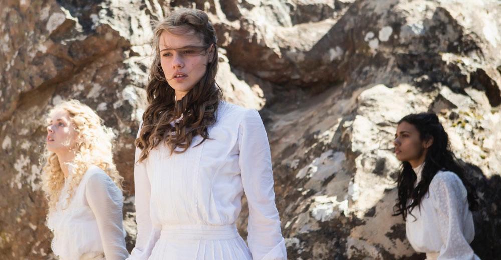Die Schülerinnen Irma, Miranda und Marion erkunden in weißen Kleidern die Felslandschaft.
