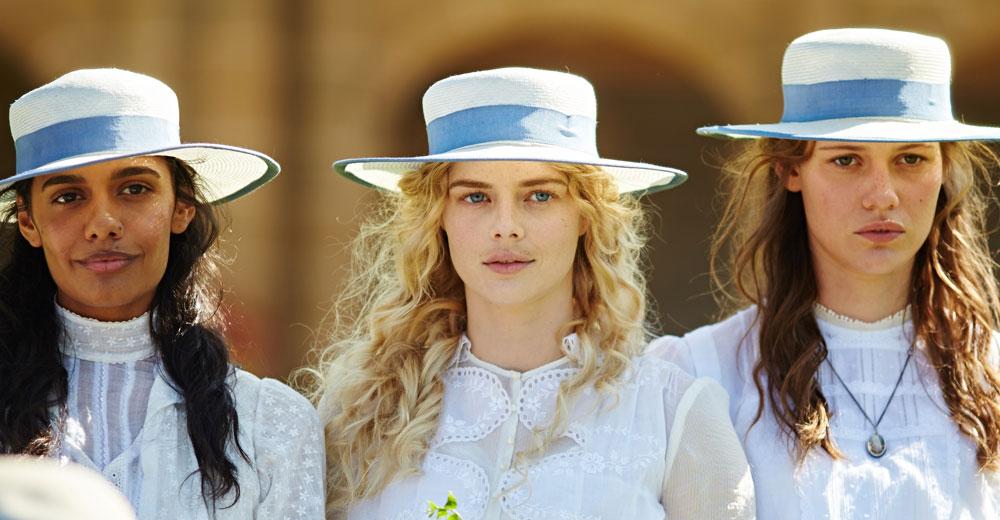 Marion, Irma und Miranda stehen in weißen Kleidern und mit weißen Hüten auf dem Schulhof.
