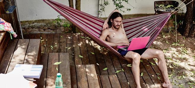 Im Urlaub streamen: Mann in Hängematte schaut Serie auf dem Laptop