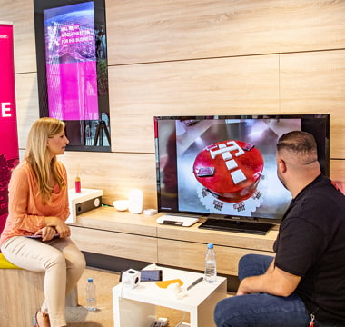 Der Tortenboss im Studio betrachtet mit Moderatorin Torten-Kreation auf Flachbildfernseher